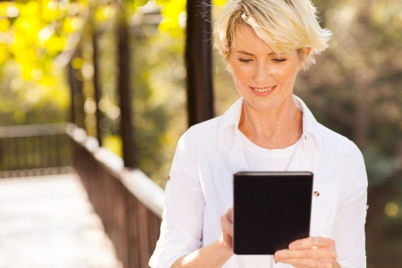 middle aged: beautiful senior woman using tablet computer outdoors
