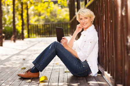 beautiful mid age woman using tablet computer outdoors