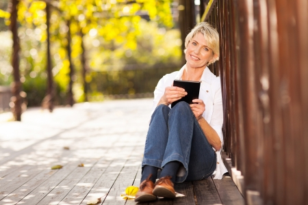 pretty middle aged woman holding tablet computer sitting outdoors photo