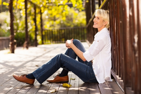 happy mid age woman sitting outdoors daydreaming