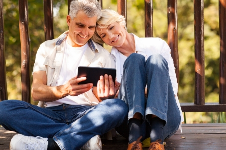 ao ar livre: casal de idosos alegre usando o computador tablet no exterior