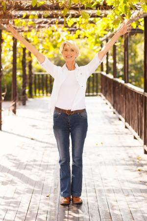 gelukkig midden leeftijd vrouw met uitgestrekte armen, buitenshuis
