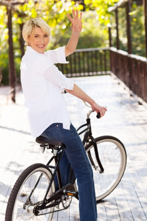 cheerful middle aged woman in a bike waving goodbye photo