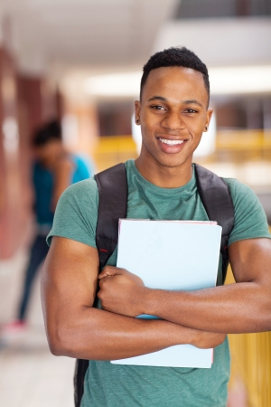 universities: cheerful african american college student holding books