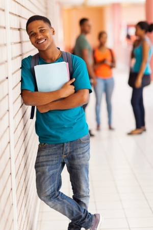 handsome african college boy standing with books against the wall photo