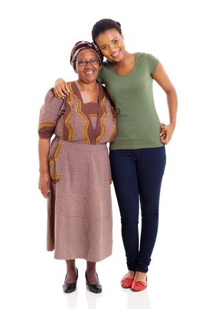 cheerful african daughter and senior mother standing on white background photo