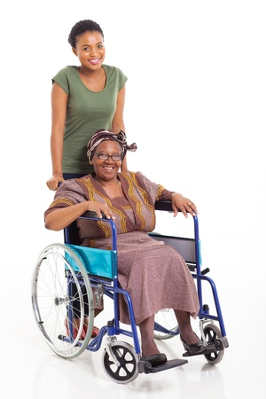 caring african daughter pushing senior mother on wheelchair over white background photo