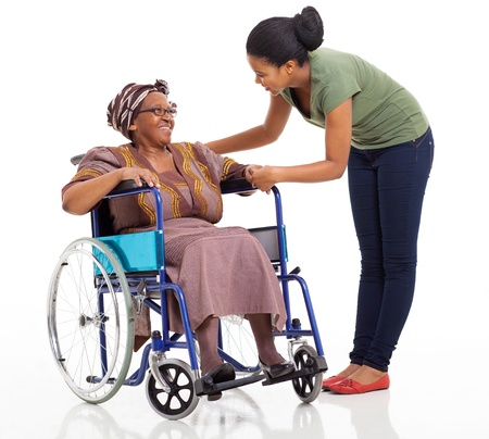 caring african girl talking to disabled senior mother on white background photo