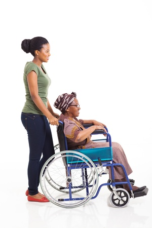 beautiful young african woman pushing grandmother on wheelchair isolated on white Stock Photo - 22062935