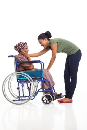 caring african woman comforting disabled senior mother on white background photo