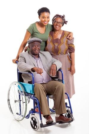 persona en silla de ruedas: sonriente hombre africano con discapacidad con la esposa y la hija aislada en blanco Foto de archivo