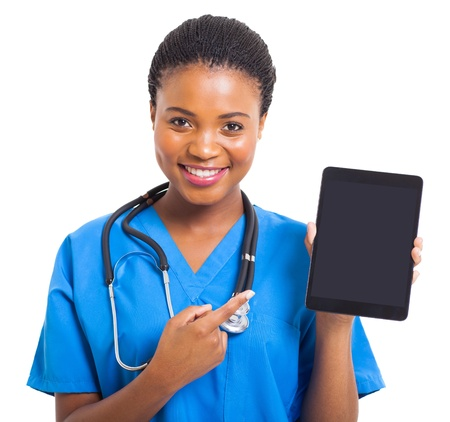 pretty african american nurse pointing tablet computer on white background photo