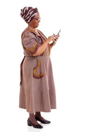 ethnic attire: side view of african woman using tablet computer on white background Stock Photo