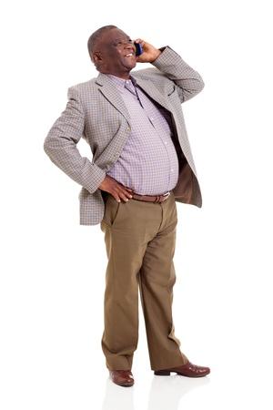 persona de pie: alegre hombre africano hablando por tel�fono celular aislado en el fondo blanco Foto de archivo