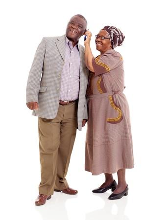jubilados: pareja africana feliz senior utilizando el teléfono móvil aisladas sobre fondo blanco