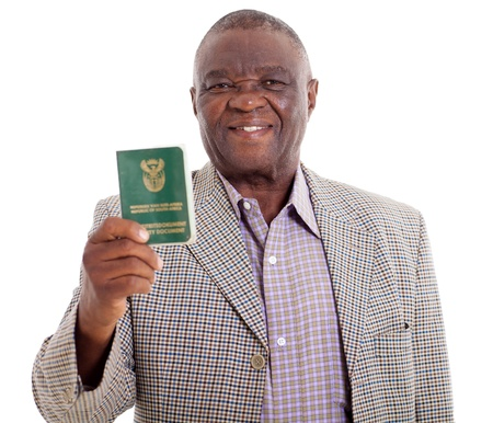 voter: smiling senior south african man holding ID book on white background Stock Photo