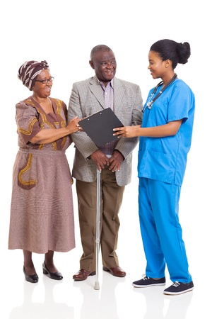 young female african nurse talking to senior couple isolated on white background photo