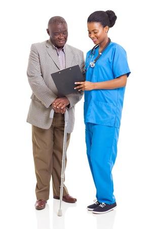 paciente: hermosa joven africano trabajador de la sanidad y al paciente mayor aislados en blanco