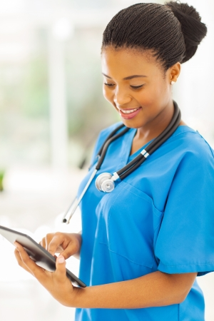 pretty afro american nurse using tablet pc photo