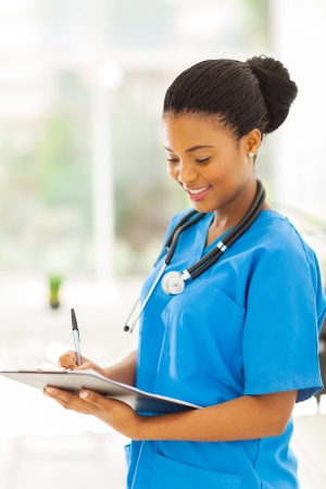 happy nurse: smiling young african medical intern doctor writing on clipboard in office