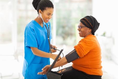 lachende african verpleegkundige controle van de bloeddruk hogere patiënt Stockfoto