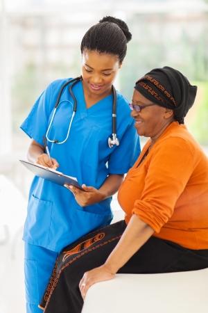 paciente: hermosa enfermera joven africano explicando resultado de la prueba m�dica a paciente senior
