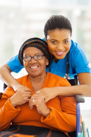 nurse and patient: portrait of senior african disabled woman and her caregiver Stock Photo