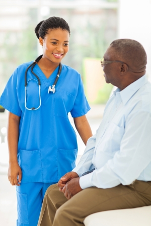 checkup: beautiful african medical doctor talking to seniot man Stock Photo