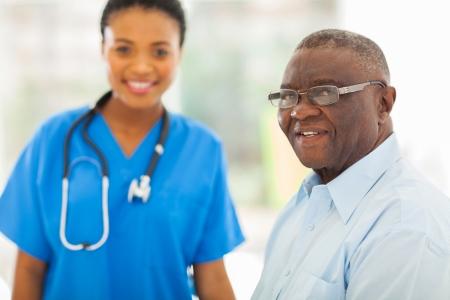 Office uniforms: mayor sonriente hombre afroamericano en oficina de los m�dicos con la enfermera en el fondo