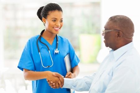 vriendelijke Afro-Amerikaanse medisch verpleegkundige handenschudden met hogere patiënt Stockfoto