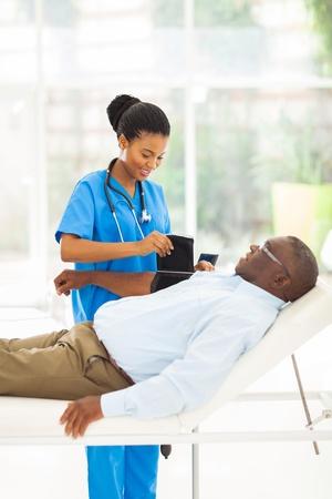 hipertension: enfermera muy africano medir la presión arterial paciente mayor