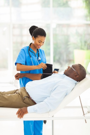 pretty african female nurse measuring senior patient blood pressure photo