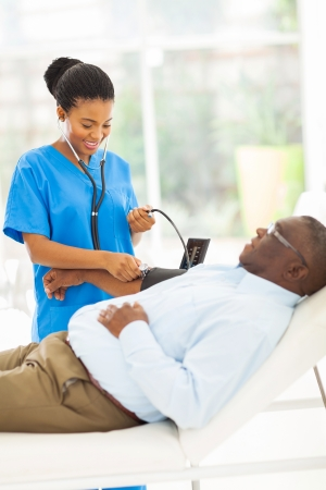 friendly young african doctor checking senior patients blood pressure