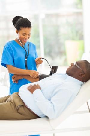 hipertension: presi�n arterial amistosa joven africano m�dico comprobaci�n de paciente mayor Foto de archivo