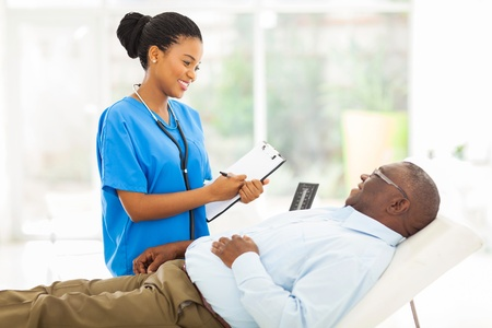 beautiful african female doctor consulting senior patient in office photo