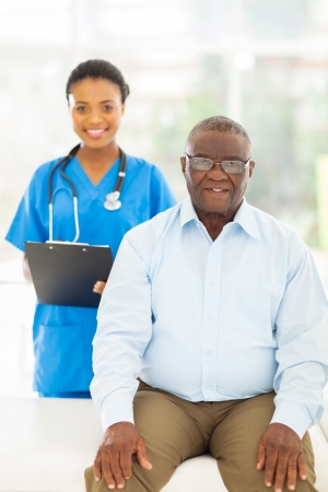 senior afro american patient in doctors office with nurse on background photo
