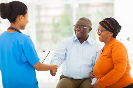 friendly african female nurse greeting senior couple in hospital photo