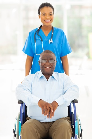 pretty african health care worker and disabled senior patient  photo