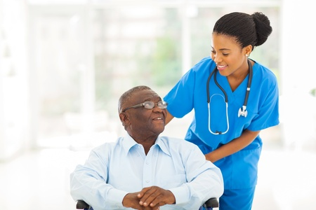 beautiful african nurse taking care of senior patient in wheelchair photo