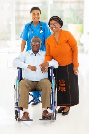 giver: Retrato de trabajador de la salud femenina africana con pareja de ancianos en el hogar
