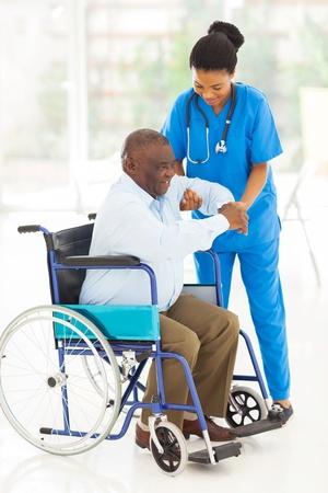 giver: amigable cuidador africano ayuda al hombre mayor de levantarse de silla de ruedas Foto de archivo
