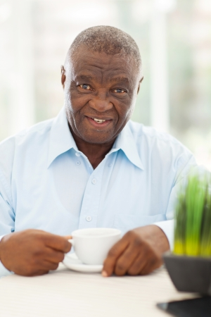 cute elderly african american man having coffee at home photo