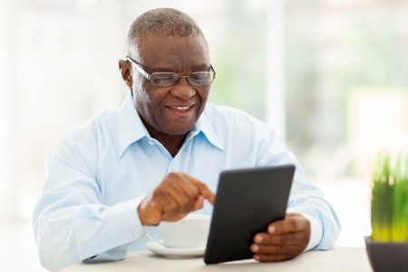 reading glasses: cheerful senior african american man using tablet computer at home Stock Photo