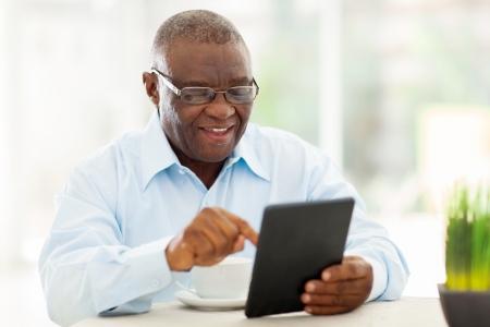 vrolijke senior Afro-Amerikaanse man met behulp van tablet-computer thuis