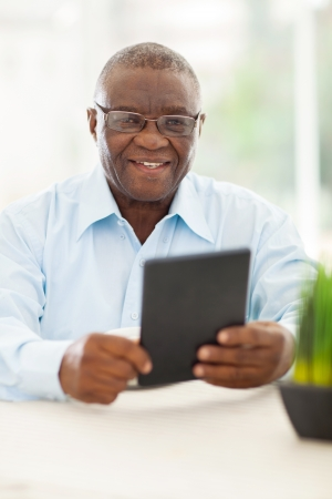 african american man: happy senior african man holding tablet computer at home