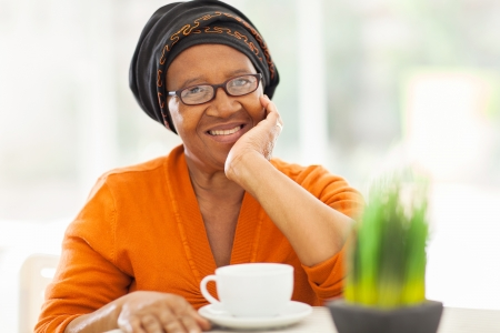 elegant senior african woman having tea at home photo