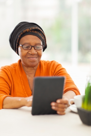 old pc: senior african woman using tablet computer at home Stock Photo