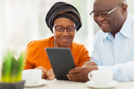 famille africaine: beau couple afro personnes âgées utilisant un ordinateur tablette à la maison