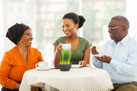 drinking tea: loving senior african parents having coffee with daughter indoors Stock Photo