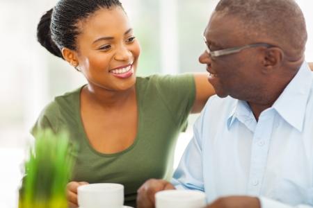 lachende oudere Afro-Amerikaanse man genieten van koffie met zijn granddaughteer thuis